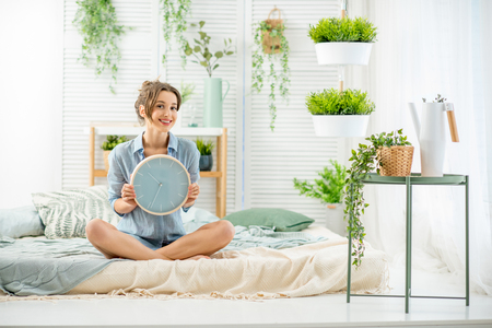Portrait of a young woman with alarm clock sitting in the beautiful and bright bedroom with green plants Stockfoto - 97459077
