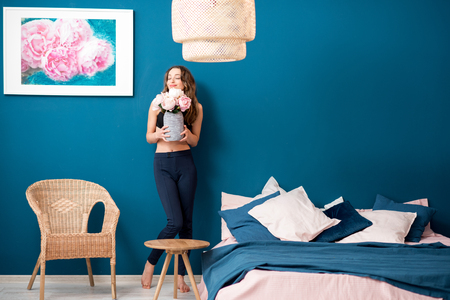 Beautiful young woman holding flowers standing in the cozy bedroom on the blue wall background at home Banco de Imagens