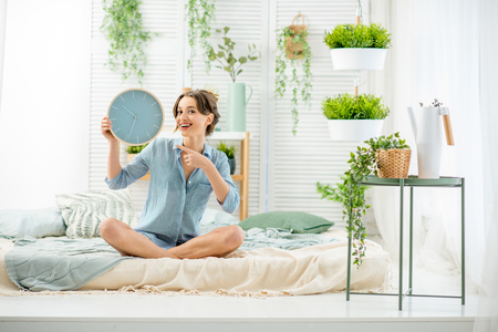 Portrait of a young woman with alarm clock sitting in the beautiful and bright bedroom with green plants