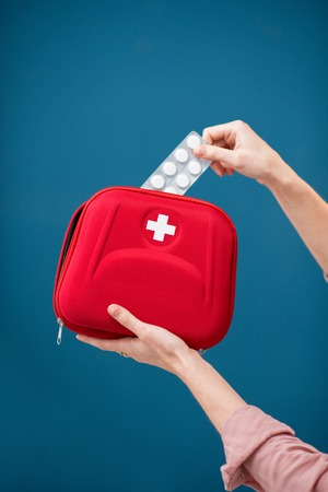 Getting a pills from first aid kit on the blue wall background