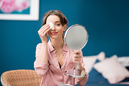 Young woman removing makeup with a cotton swab sitting in the blue bedroom Stock Photo