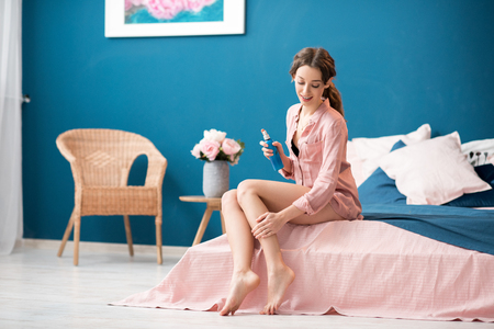Young woman applying a lotion on her legs sitting on the bed in the beautiful pink and blue bedroom interior