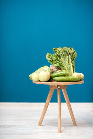 Table with healthy green food on the blue background indoors Foto de archivo