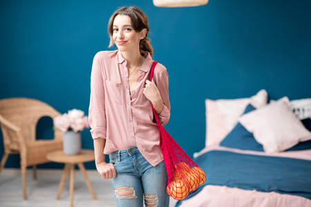 Portrait of a young woman standing with red bag full of oranges in the blue and pink bedroom at home Stock Photo