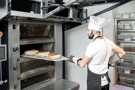 Baker taking off baked breads with shovel from the professional oven at the manufacturing Foto de archivo