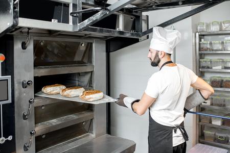 Piekarz zdejmujący wypiekane pieczywo łopatą z profesjonalnego pieca przy produkcji Zdjęcie Seryjne