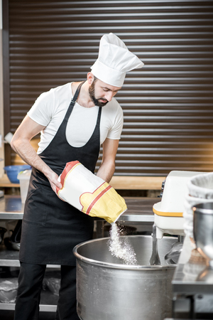 Handsome baker in uniform filling flour into the professional kneader for bread baking at the bakery Foto de archivo