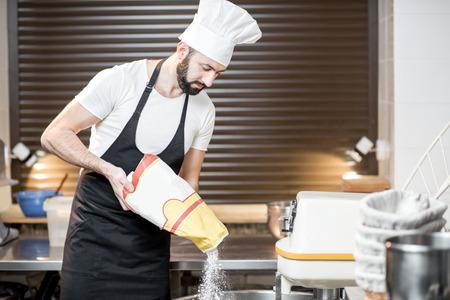 Beau boulanger en farine de remplissage uniforme dans le pétrin professionnel pour la cuisson du pain à la boulangerie Banque d'images