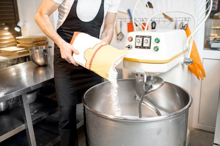 Remplissage de farine dans le pétrin professionnel pour la cuisson du pain dans la boulangerie