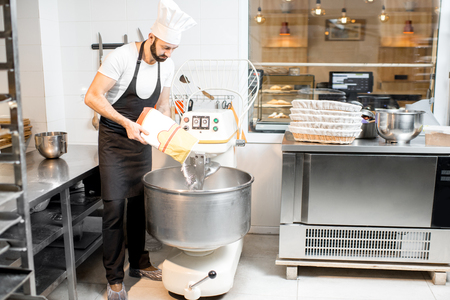 Handsome baker in uniform filling flour into the professional kneader for bread baking at the bakery Zdjęcie Seryjne