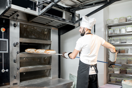 Baker taking off baked breads with shovel from the professional oven at the manufacturing Stockfoto
