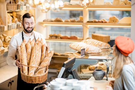 Handsome bread seller with basket full of baguettes and female customer in the beautiful store with bakery products Stock Photo