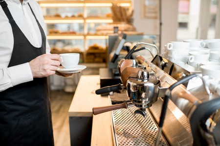 Barista making coffee with professional coffee machine in the cafe Stock Photo