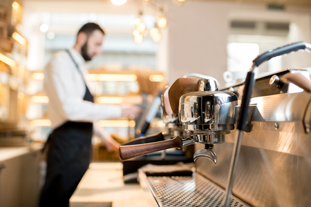 Professional coffee machine in the cafe with barista on the background