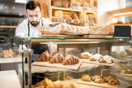 Verkäufer, der köstliche Hörnchen auf den Ladenschaukasten des Bäckereihauses setzt Standard-Bild