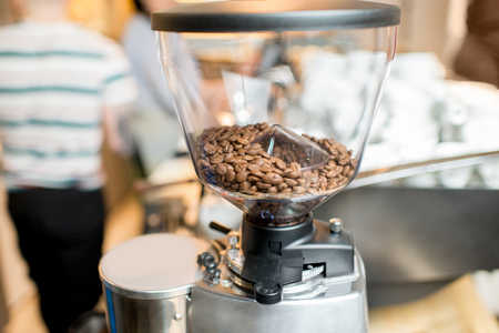 Close-up view on the coffee grinder with coffee beans in the cafe