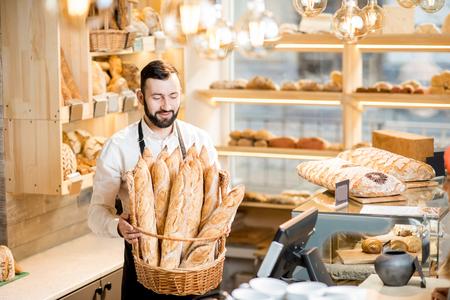 Hübscher Brotverkäufer mit dem Korb voll von den Stangenbroten im schönen Speicher mit Bäckereiprodukten Standard-Bild