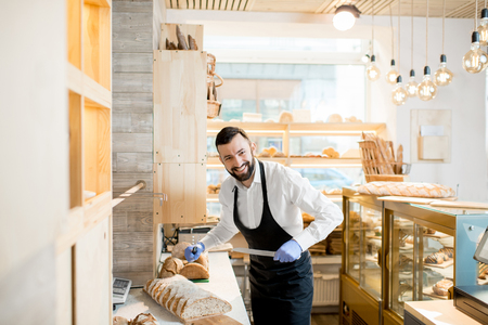 Funny portrait of a man seller cutting a fresh bread for selling in the store with bakery products