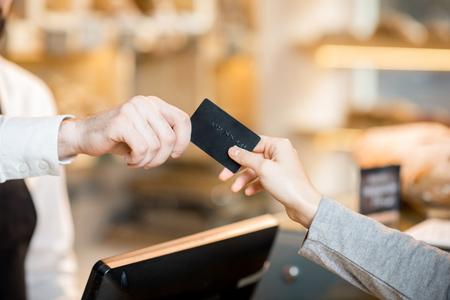 ベーカリー製品で店内のクレジットカードで支払う。手とカードのクローズアップビュー