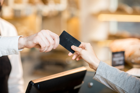 Paying by credit card in the store with bakery products. Close-up view on the hands and card