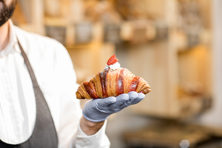 Holding delicious croissant with raspberry in the bakery store