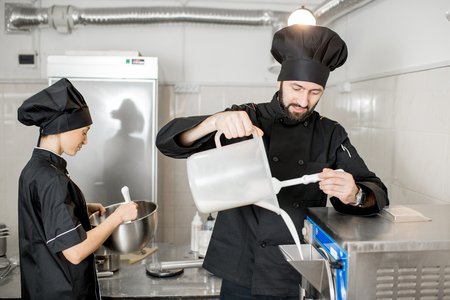 Chef pouring basis into the ice cream freezer machine in the small manufacturing Фото со стока
