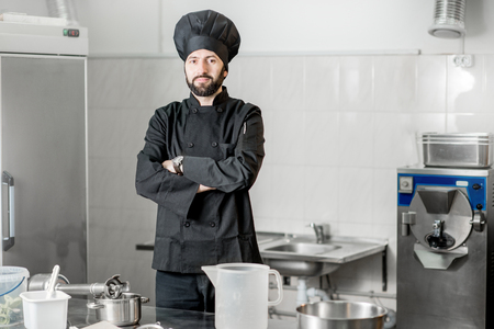 Portrait of a chef cook standing in the professional kitchen during the process of ice cream making