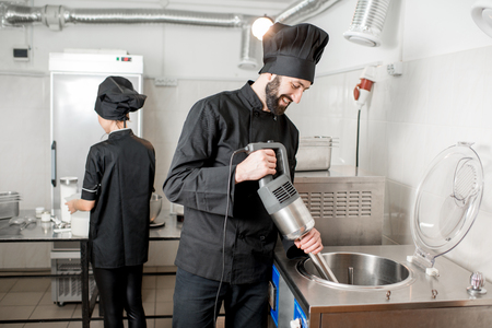 Chef cook mixing milk in pasteurization machine prepairing basis for ice cream production with young woman assistant