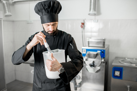 Chef cook checking milk for ice cream production standing in the small ice cream manufacturing