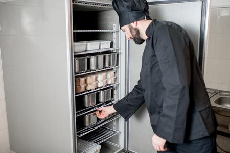 シェフは、キッチンでプロの冷蔵庫から食材とトレイを取得します