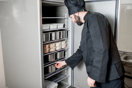 Chef cook getting a tray with ingredients from the professional refrigerator in the kitchen