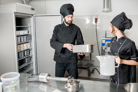 Chef cook with young woman assistant making ice cream standing in the professional kitchen Stockfoto