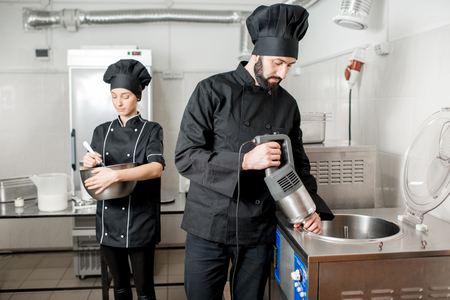 Chef cook mixing milk in pasteurization machine prepairing basis for ice cream production with young woman assistant Фото со стока - 97851491