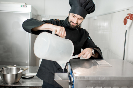 Chef pouring basis into the ice cream freezer machine in the small manufacturing 版權商用圖片