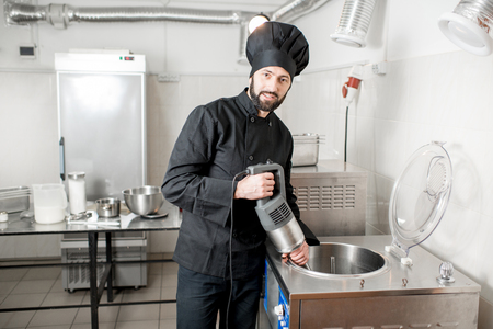 Chef cook mixing milk in pasteurization machine prepairing basis for ice cream production