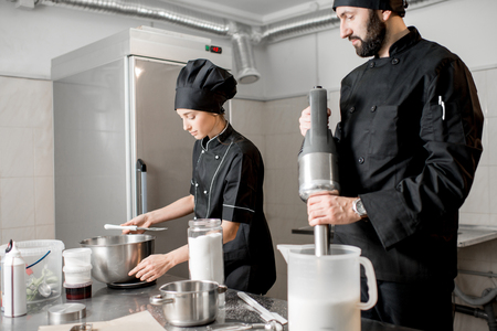 Chef cook with young woman assistant making ice cream together mixing ingredients in the professional kitchen of the small manufacturing Stockfoto