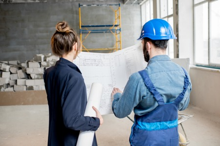 Foreman expertising the structure with businesswoman holding a blueprints at the construction site indoors Banque d'images - 98268916