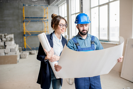 Foreman expertising the structure with businesswoman holding a blueprints at the construction site indoors Banque d'images - 99582706
