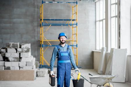 Portrait d & # 39 ; un constructeur dans un uniforme de travail avec casque de protection debout avec des instruments au chantier de construction intérieur Banque d'images - 98268921