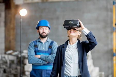 Woman client wearing VR glasses imagining future interior standing with builder at the construction site Reklamní fotografie - 99582710