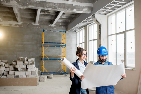 Foreman expertising the structure with businesswoman holding a blueprints at the construction site indoors Banque d'images - 99571265