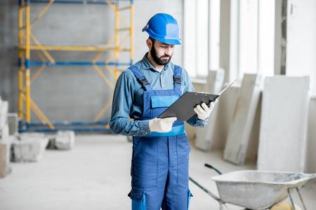 Builder ou contremaître dans le travail uniforme travaillant la pièce d & # 39 ; intérieur avec dossier à l & # 39 ; intérieur du chantier de construction Banque d'images - 98269201