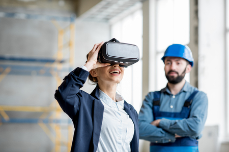 Woman client wearing VR glasses imagining future interior standing with builder at the construction site