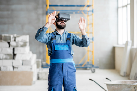 Builder projecting with VR glasses future interior standing at the construction site 版權商用圖片
