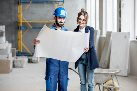 Foreman expertising the structure with businesswoman holding a blueprints at the construction site indoors Banque d'images - 99571033