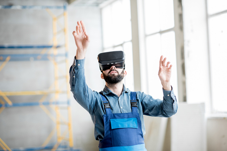 Builder projecting with VR glasses future interior standing at the construction site Stock Photo