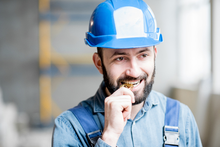 Portrait of a builder in working uniform biting cryptocoin at the construction site indoors Stockfoto