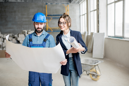 Foreman expertising the structure with businesswoman holding a blueprints at the construction site indoors Banque d'images - 99571035