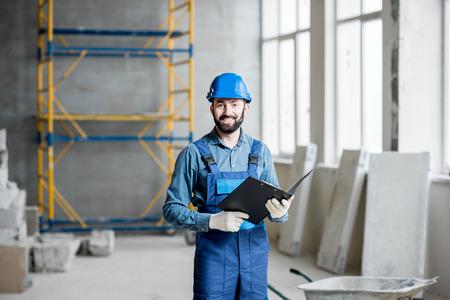 Builder ou contremaître dans le travail uniforme travaillant la pièce d & # 39 ; intérieur avec dossier à l & # 39 ; intérieur du chantier de construction Banque d'images - 98269474