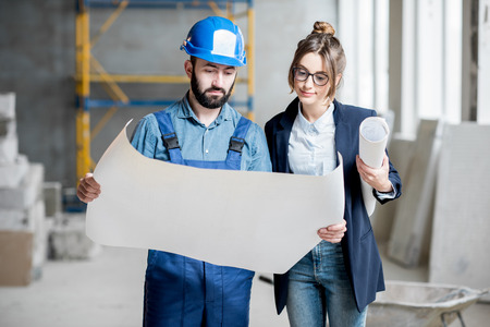 Foreman expertising the structure with businesswoman holding a blueprints at the construction site indoors Stock Photo